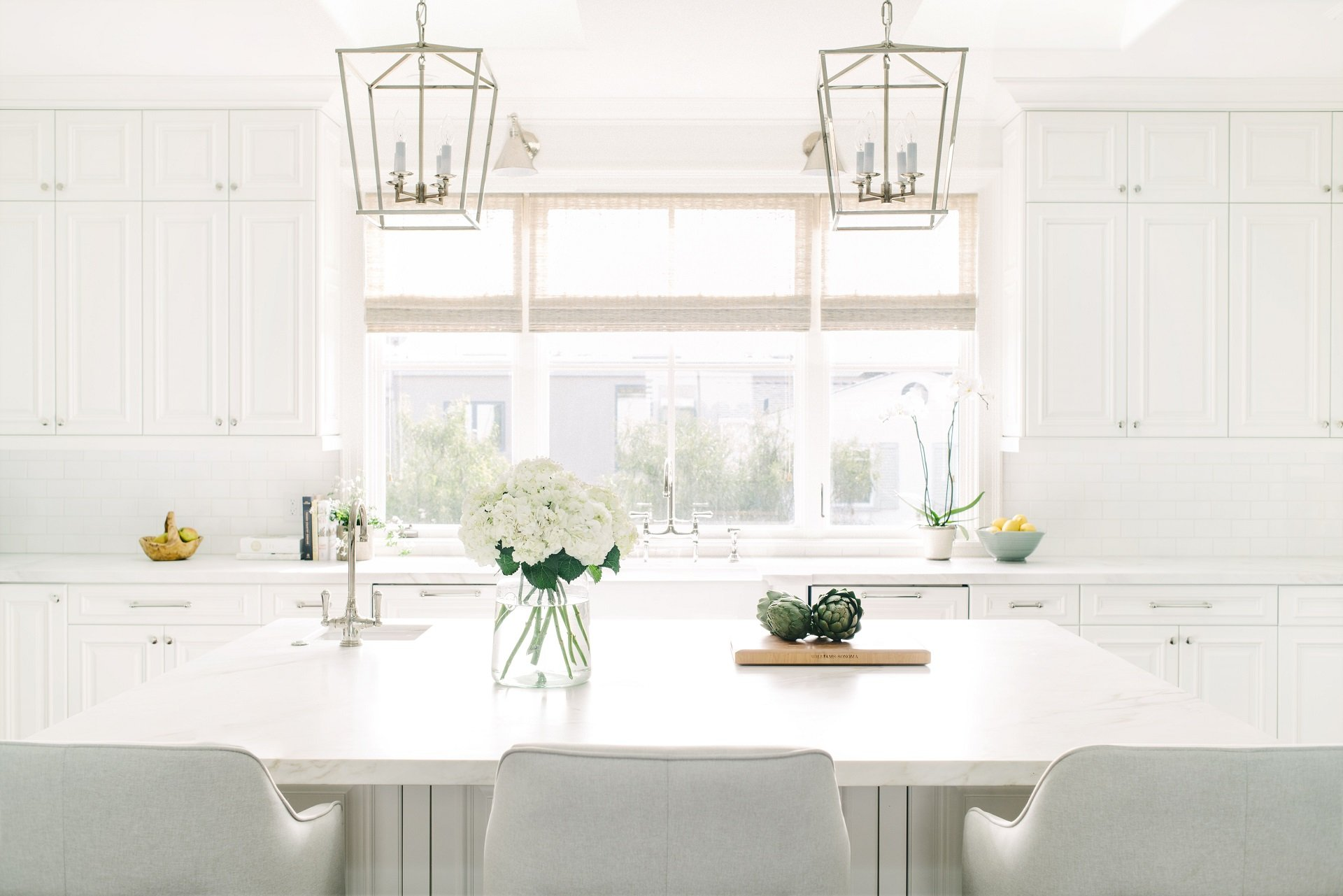 California beach house kitchen all white and sunny with modern light fixtures