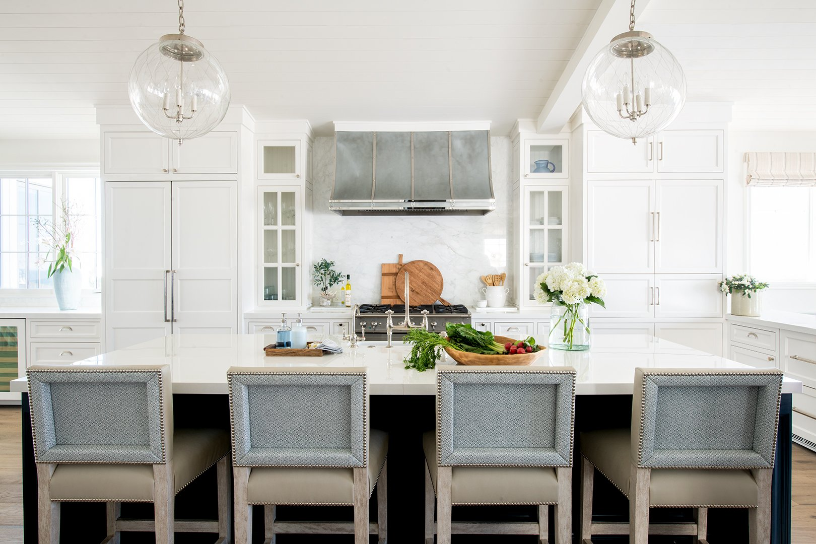 Kid friendly kitchen with marble-lookalike porcelain counter tops and faux leather chairs at the eat-in island