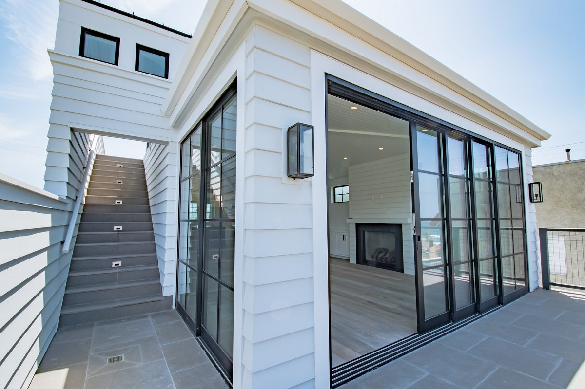 Top story of modern beach house with floor to ceiling window and door that opens onto a patio with a view