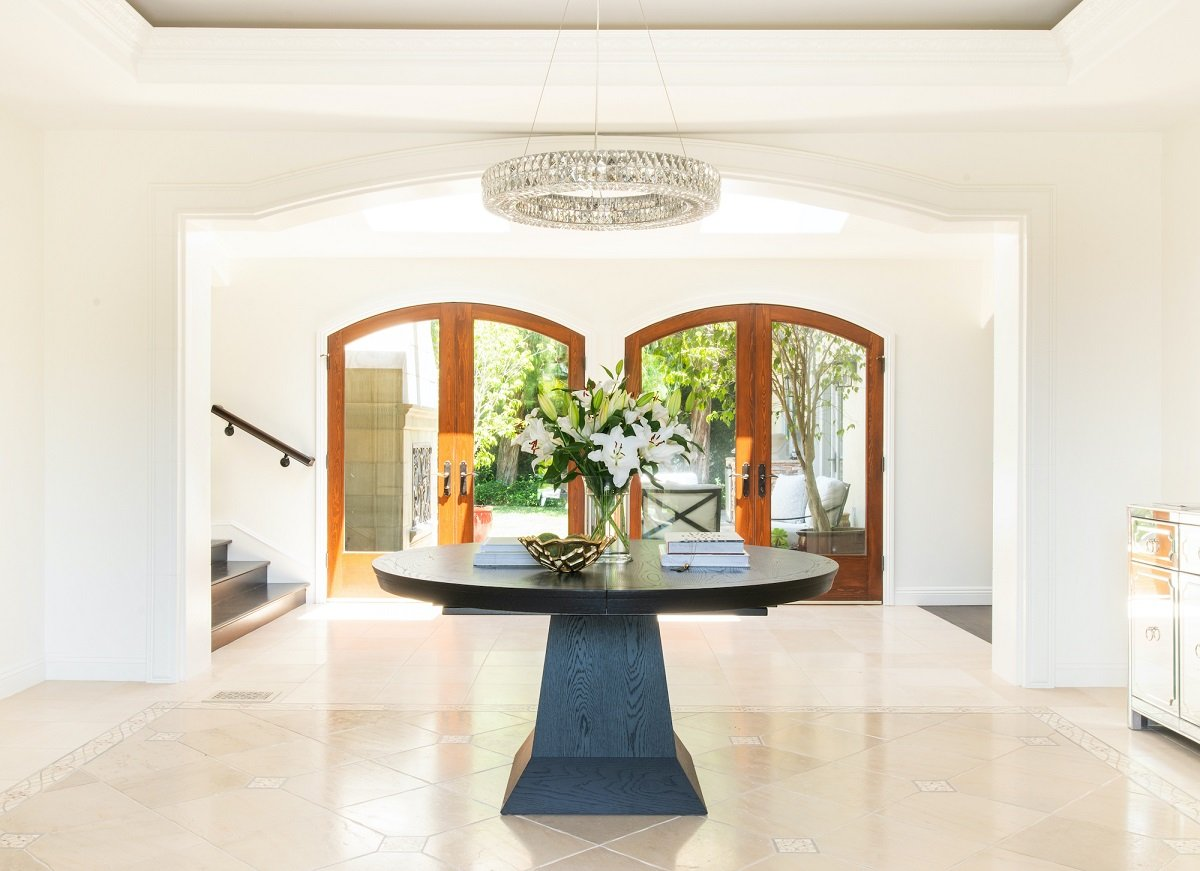Double French doors framed in solid wood in entryway of Mediterranean mansion