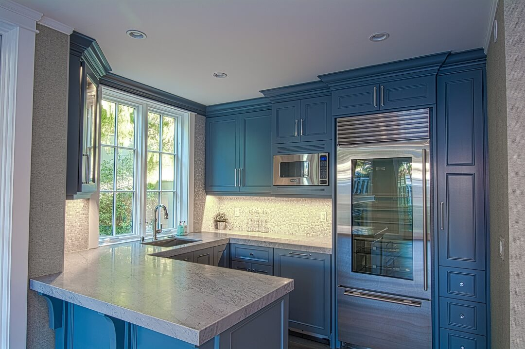 California beach house kitchen with custom blue cabinets and granite counters
