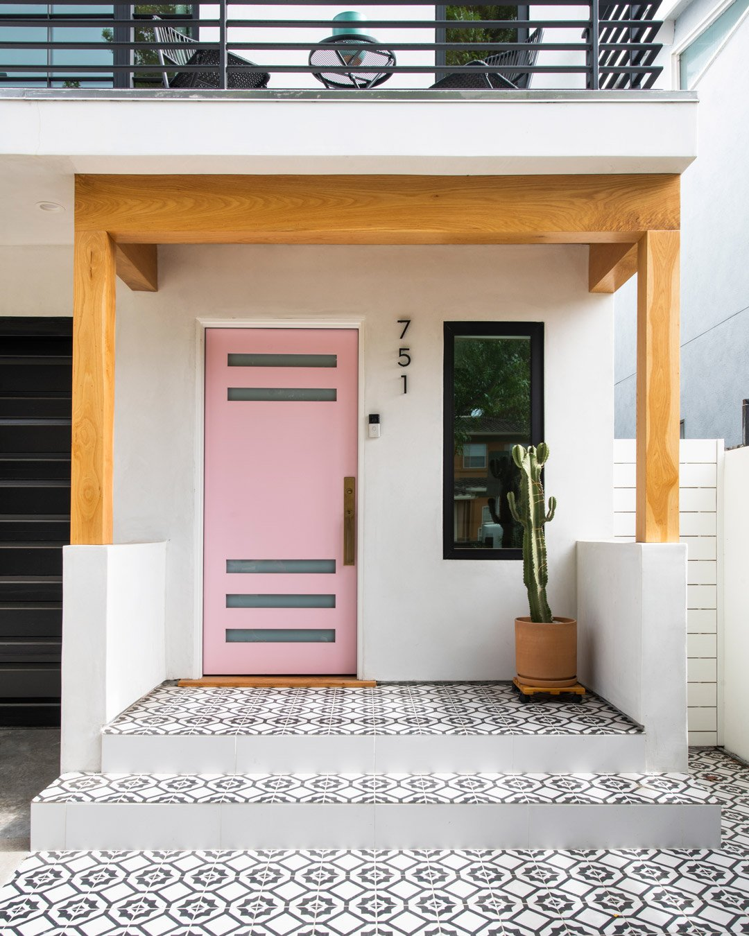 California modern stucco exterior entryway with pink art deco door and Spanish tile
